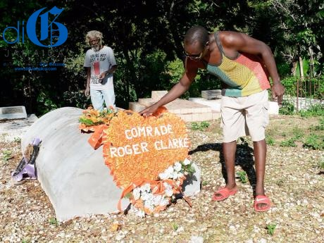 Stacy Wilson adjusts a wreath at the grave of Roger Clarke in the community of Williamsfield, Central Westmoreland.