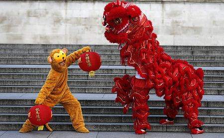 A lion dancer and a performer in a monkey costume pose at Trafalgar Square in London, Monday, Feb. 8, 2016. The Chinatown Chinese Association (LCCA) welcomed the Chinese New Year of the Monkey in Trafalgar Square with a photo call. (AP Photo/Frank Augstein)