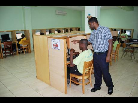 Boys inside the St John Bosco Boys' Home's computer room being guided by an instructor.