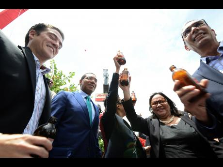 The beer flowed freely at 10 a.m. Wednesday September 7, 2016 at the resumption of exports of Red Stripe beer to the United States. Participants in the ceremonies included, from left, Managing Director of Red Stripe Jamaica, Ricardo Nuncio; Prime Minister Andrew Holness; Head of corporate relations at Red stripe, Dianne Ashton-Smith; President of the Jamaica Exporters Association, Michelle Chong; and Chairman of Red Stripe, Richard Byles.